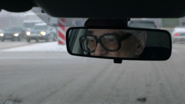 Человек за рулем в зимнем городе Premium Фотографии