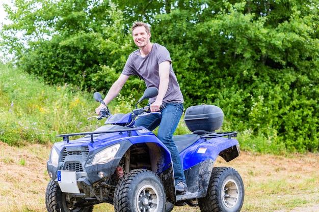 Man driving off-road with quad bike or atv Premium Photo
