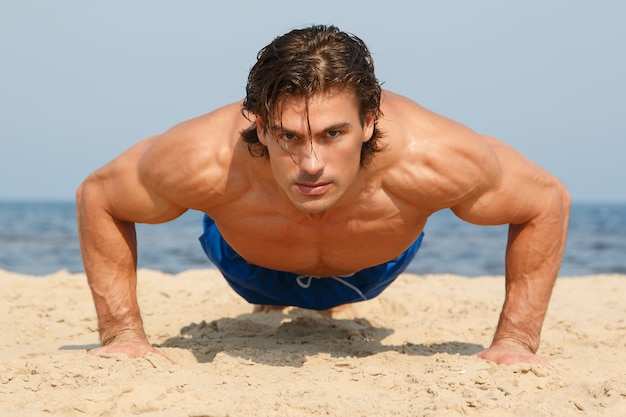 Man during workout on the beach Premium Photo