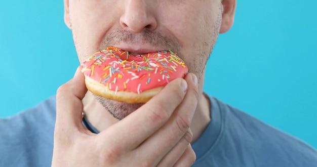 Man eat donut closeup on blue Premium Photo