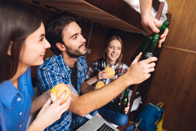 Man eat hamburgers with girls and cheers with guy. Premium Photo