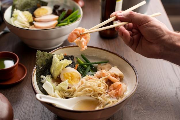 Человек ест азиатские рамэн с креветками и лапшой в ресторане Premium Фотографии