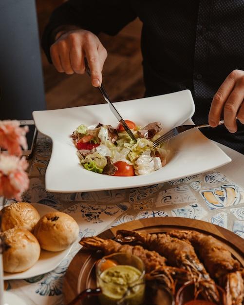 Man eating caesar salad with mixed ingredients Free Photo