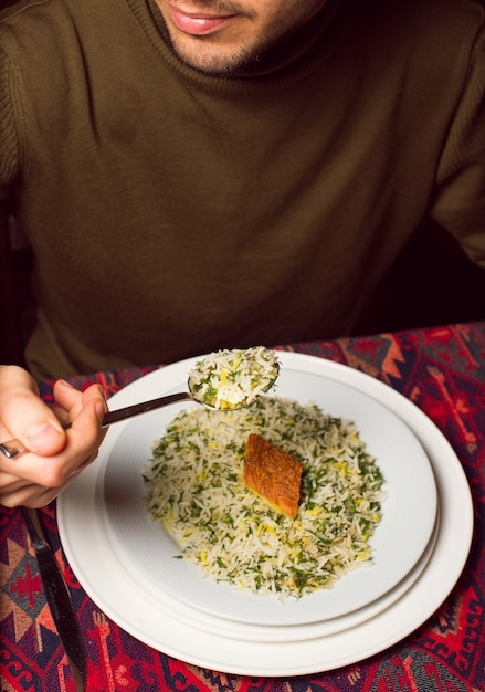 Man eating chigirtma sebzi plov, rice garnish with vegetables and herbs Free Photo