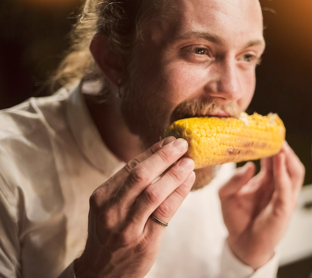 Man eating corncob with pleasure Free Photo