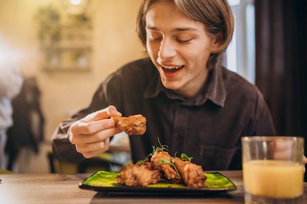 카페에서 소스와 함께 프라이드 치킨을 먹는 남자 무료 사진