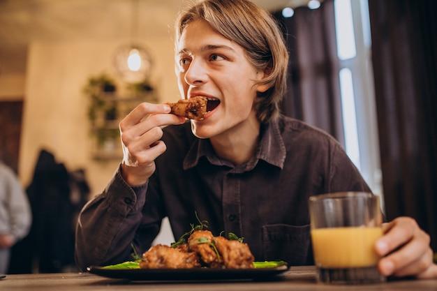 カフェでフライドチキンとソースを食べる男 無料写真