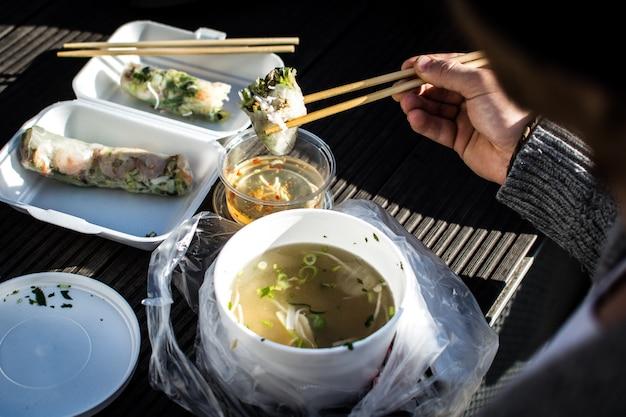 Man eating his take away vietnamese food with chopsticks outside Free Photo