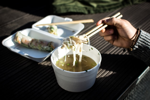 Man eating his take away vietnamese food with chopsticks outside Free Photo