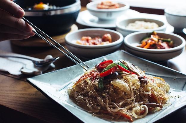 젓가락으로 한국 유리 국수를 먹는 남자 무료 사진