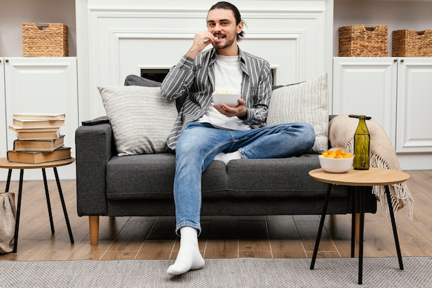 팝콘을 먹고 Tv를 시청하는 남자 무료 사진