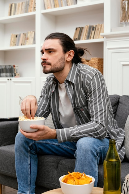 팝콘을 먹고 Tv 측면보기를 보는 남자 무료 사진