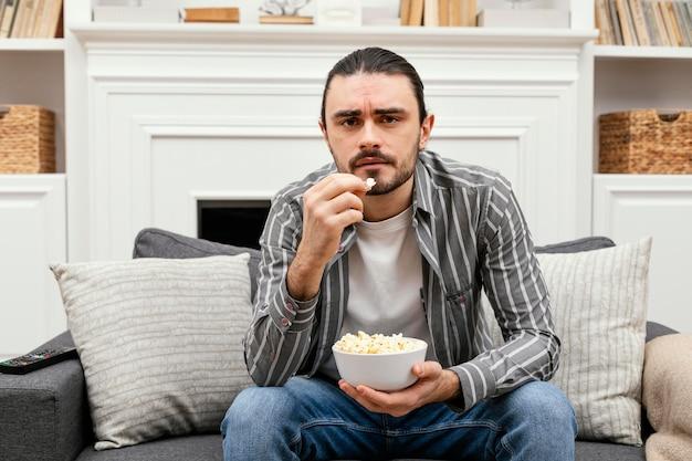 팝콘을 먹고 Tv를 보는 남자 무료 사진