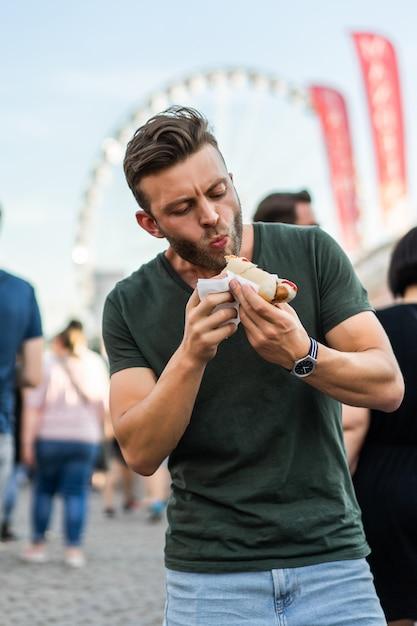 Man eating street food. street hotdogs Free Photo