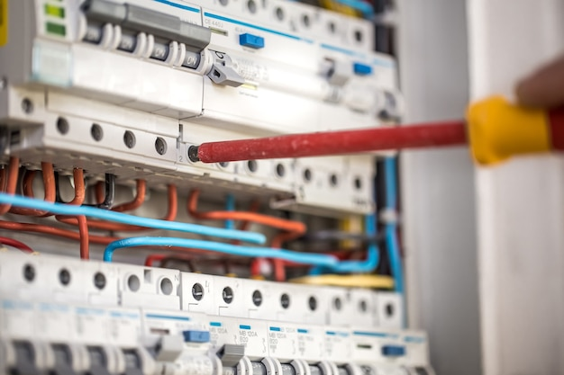 Man, an electrical technician working in a switchboard with fuses. installation and connection of electrical equipment. close up. Free Photo