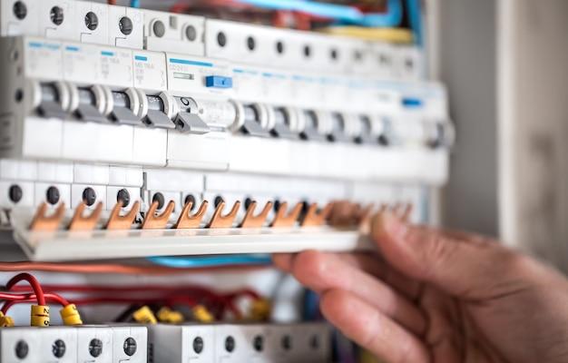 L'uomo, un tecnico elettrico che lavora in un quadro elettrico con fusibili. installazione e collegamento di apparecchiature elettriche. avvicinamento. Foto Gratuite