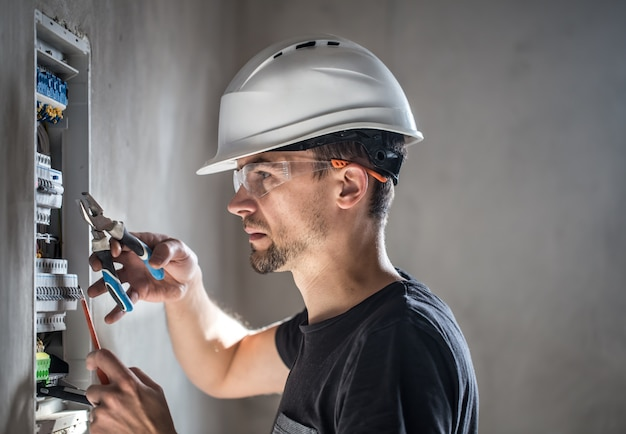 Man, an electrical technician working in a switchboard with fuses. installation and connection of electrical equipment. Free Photo