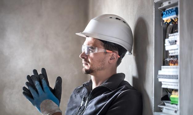 L'uomo, un tecnico elettrico che lavora in un centralino con micce. installazione e collegamento di apparecchiature elettriche. Foto Gratuite