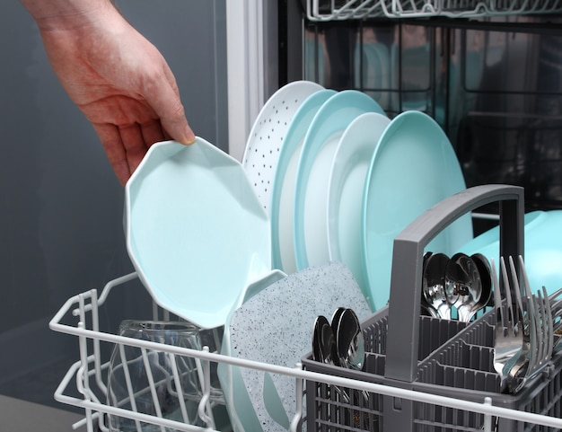 Man empty out the dishwasher in kitchen.close-up of male hands loading dishes to the dishwasher Premium Photo