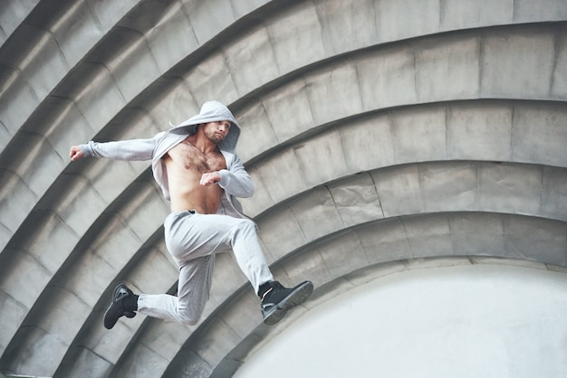 Man engaged in parkour jumping on the street workout. Free Photo