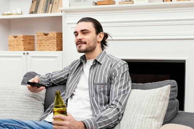 맥주를 즐기고 Tv를 보는 남자 무료 사진