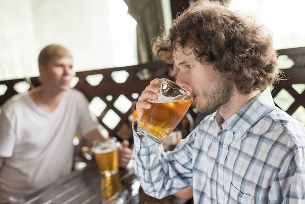 Man enjoying beer near friends in pub Free Photo