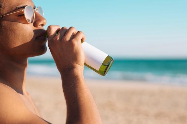 Man enjoying beer on seashore Free Photo