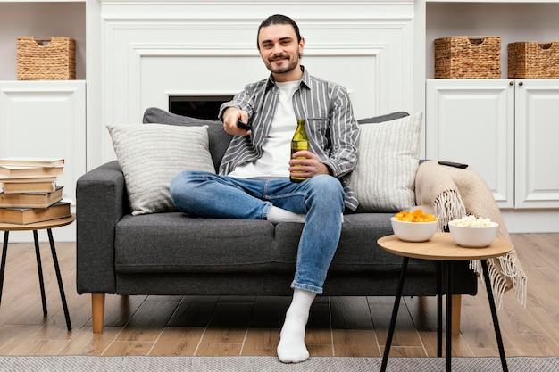 Uomo che si gode una birra e guarda la tv seduto sul divano Foto Gratuite