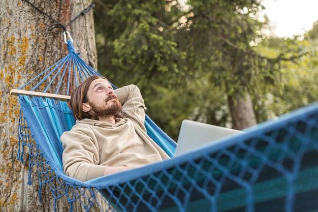 Человек, наслаждаясь свое время на природе, сидя в гамаке Бесплатные Фотографии