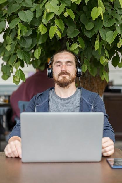 ノートパソコンのあるテラスで音楽を楽しむ男 無料写真