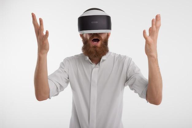 남자는 가상 현실 헤드셋을 착용하고 매혹되고 충격을받는 손을 들었다. 무료 사진