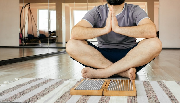Мужчина занимается йогой, медитируя, сидя руки соединились на полу возле доски садху Premium Фотографии