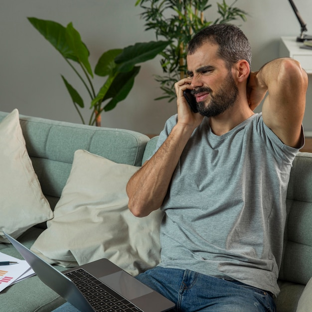 自宅からラップトップで作業中に首の痛みを経験している男性 無料写真