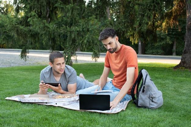 Мужчина что-то объясняет своей подруге в ноутбуке. счастливые студенты учатся в парке и улыбаются. Premium Фотографии