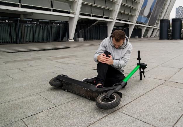 男は膝を抱えて痛みを感じてスクーターから落ちた。アスファルトの上に横たわっている緑色の電動スクーター。灰色のフーディのスタイリッシュな男が地面に座って膝の痛みを持っています。環境にやさしい輸送コンセプト。 Premium写真