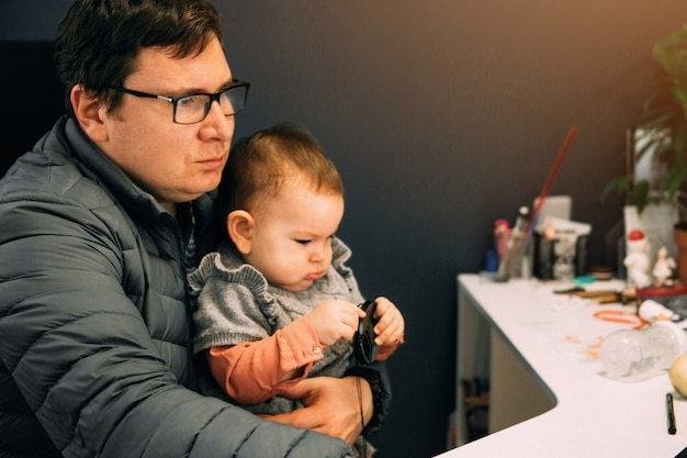 Man father with baby in carrier working at office or home with computer at the desk Premium Photo