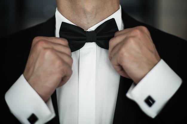 Man fies black bow tie on white shirt Free Photo