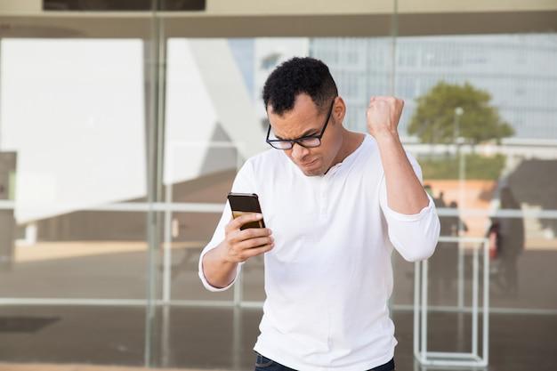 Man finishing phone call, receiving news, celebrating success Free Photo