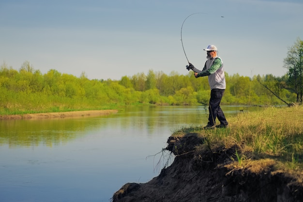 Man fish with spinning on river bank Premium Photo