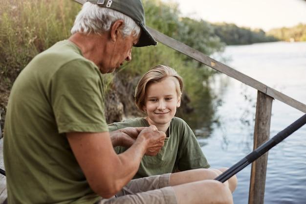 물고기를 잡는 방법으로 유명한 미끼를 연결하는 손자를 가르치는 남자 어부, 웃는 젊은 금발의 남자가 미소와 집중된 표정으로 수석 남성을 바라보고 물에 나무 계단에 앉아. 무료 사진