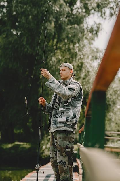 Мужчина ловит рыбу и держит удочку Бесплатные Фотографии