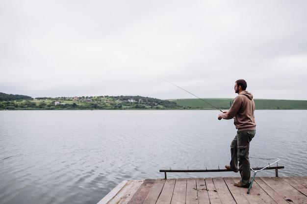 Man fishing in the calm lake Free Photo