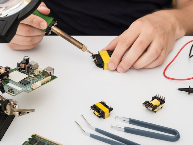 Man fixing a connector using the soldering iron Free Photo