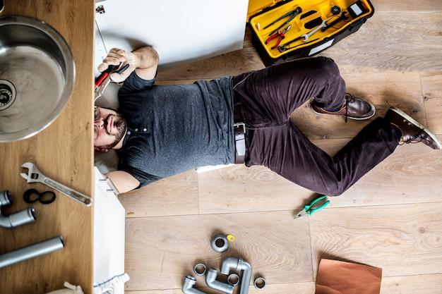 Man fixing kitchen sink Premium Photo