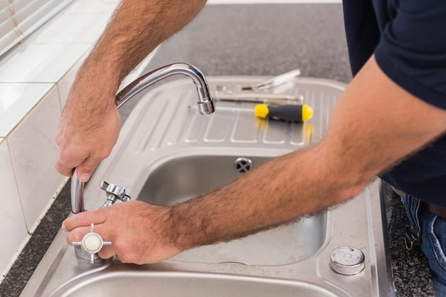 Man fixing tap with pliers Photo | Premium Download