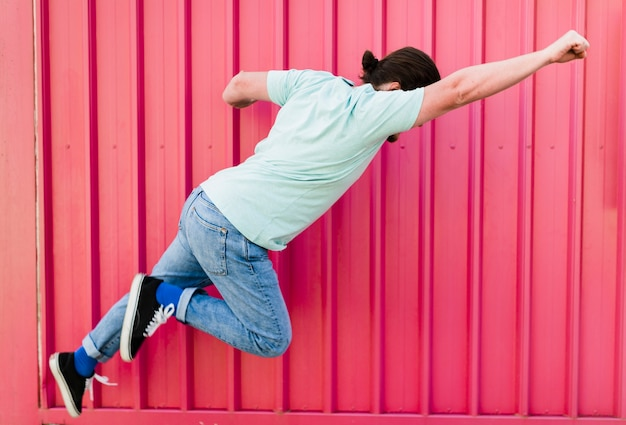 Man flying with arms raised against pink corrugated wall Free Photo