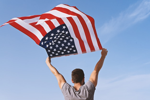Man from behind with raised hands and waving american flag Premium Photo