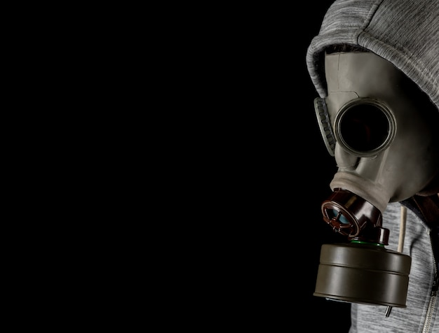 Man in a gas mask on a black background. protection against viruses Premium Photo