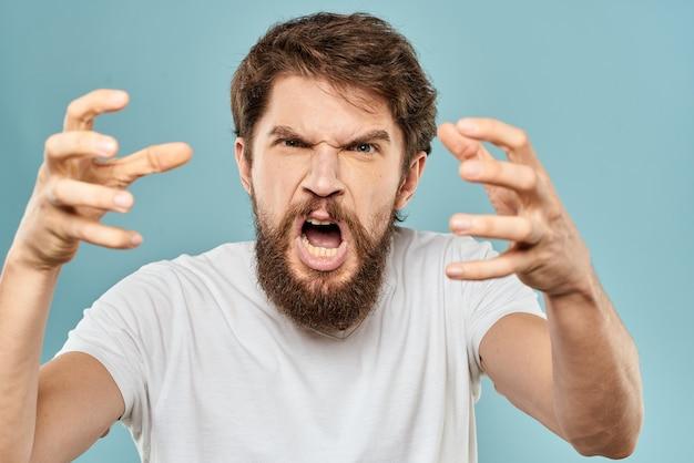 Человек жесты руками эмоции недовольство белая футболка синий фон Premium Фотографии