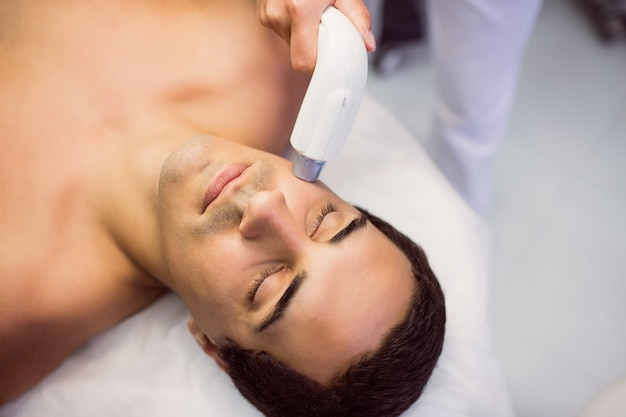 Man getting a facial massage at clinic Free Photo